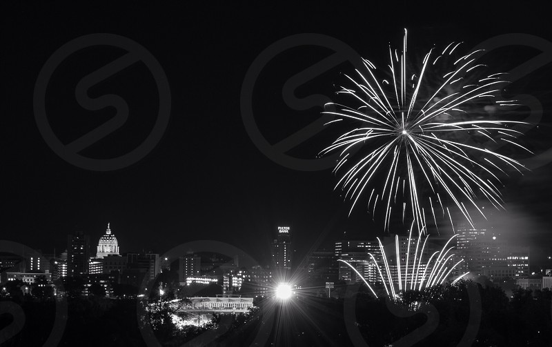 fireworks above nighttime illuminated cityscape in black and white photo