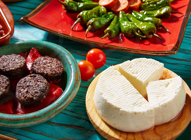 Tapas Morcilla and cheese de Burgos from Spain and padron peppers photo