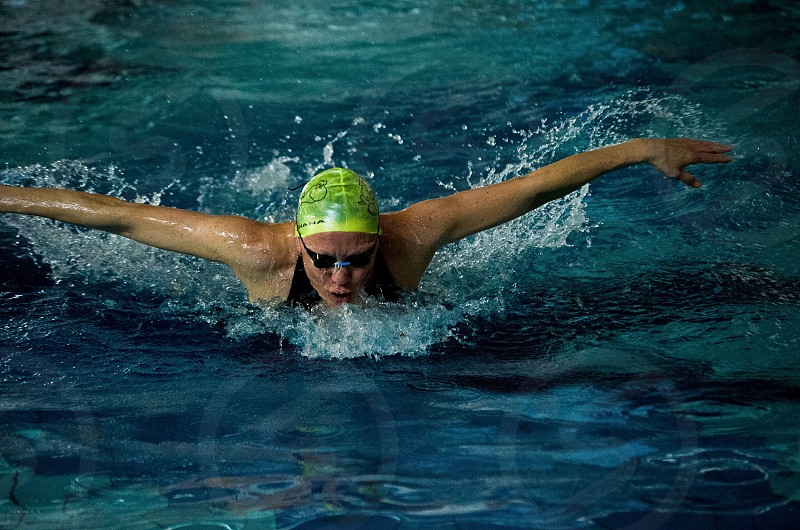 person wearing green swimming cap swimming in butterfly stroke photo