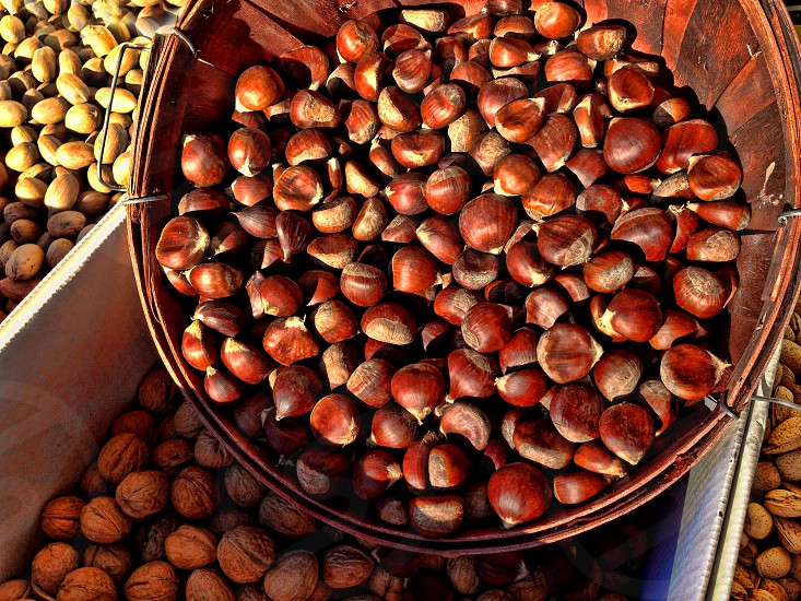 Chestnuts fill a basket; other nuts surround them. photo