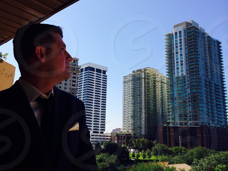 man in suit near tall buildings photo