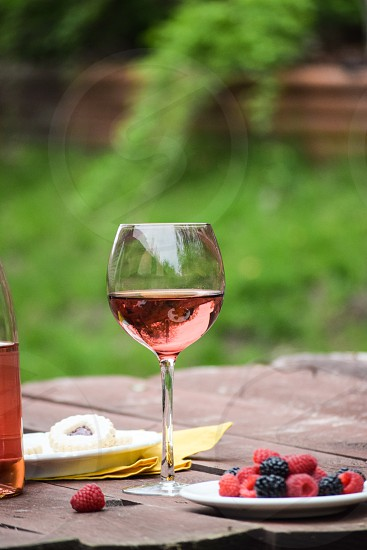 clear wine glass filled with red liquid besides blue and red lychee on selective focus photography during day time photo