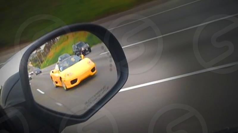 Yellow Ferrari in car side mirror photo