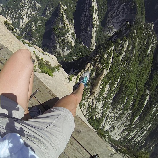 person wearing gray cargo shorts standing on cliff photo