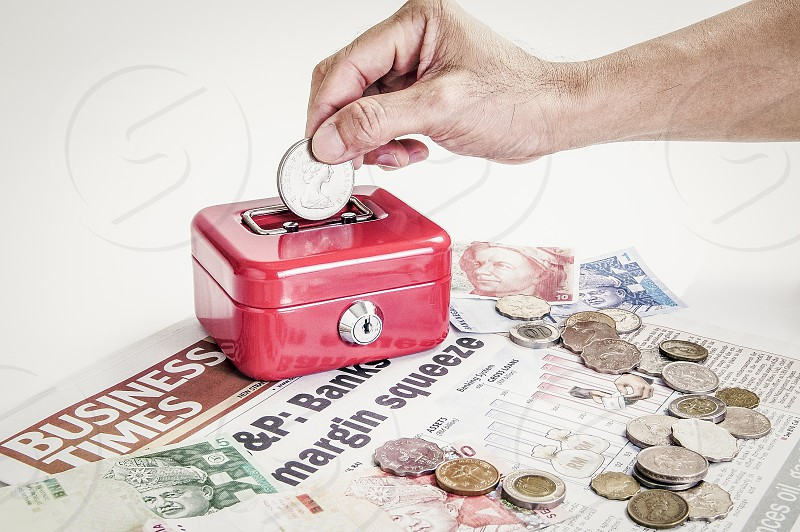 Close-up of hand putting coin into red metal cash box over business newspaper currencies and coins.  photo
