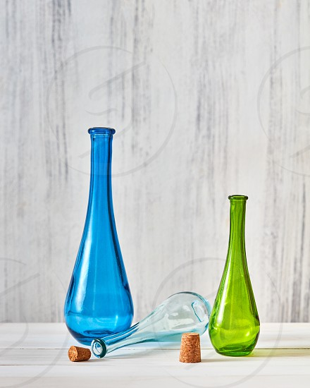 Green blue glass bottles stand on a gray background and transparent bottle lies between them on a gray with copy space. Concept of saving homemade products photo