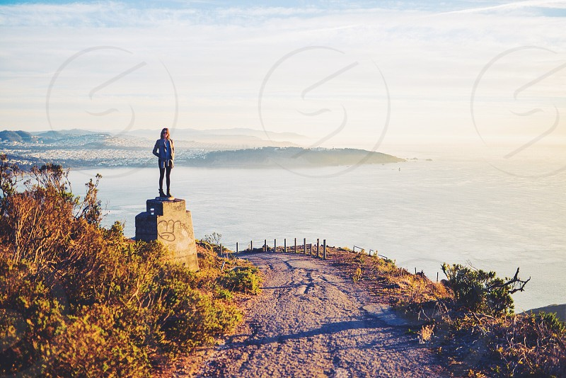 woman standing on top of rock photo