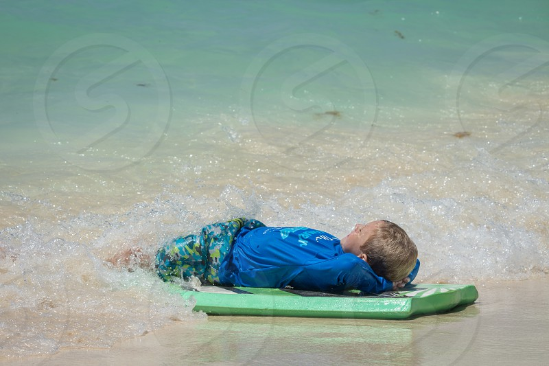 kid resting under surf table in the beach photo