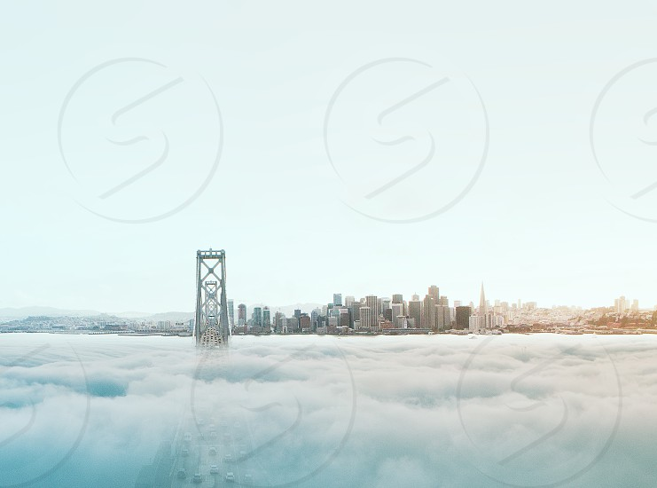 golden gate bridge almost covered with fog with a view of the city under white skies during daytime photo