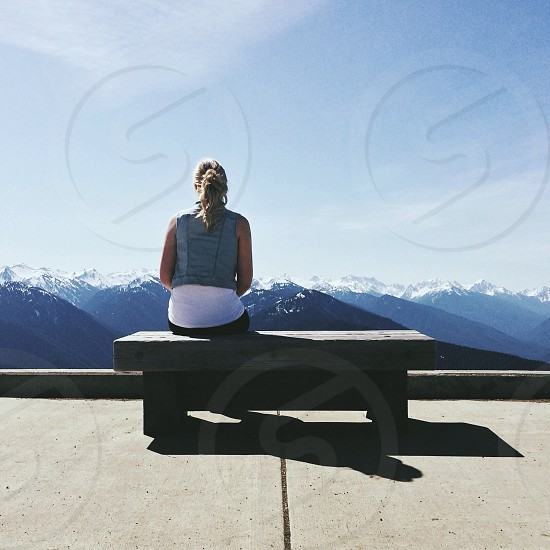 woman in a blue vest sitting on a wood bench photo