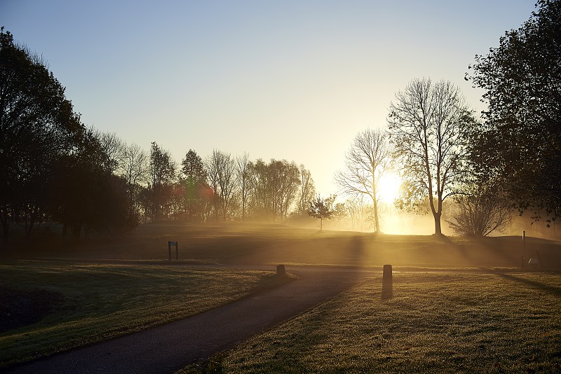 Low angle shot looking out onto a golf fairway in early morning autumn sunlight with fog photo