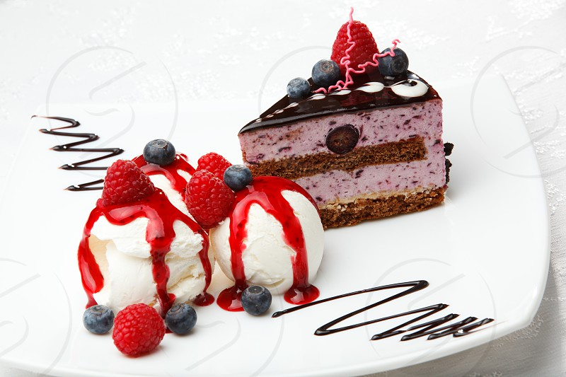Scoops of creamy vanilla ice cream topped with berry coulis served with fresh blueberries and raspberries and a slice of gourmet chocolate and berry cake photo