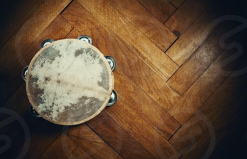 Old wooden tambourine on brown parquet.  photo