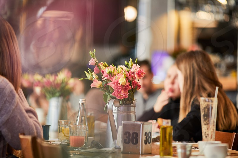 Table with flowers and people setting around photo