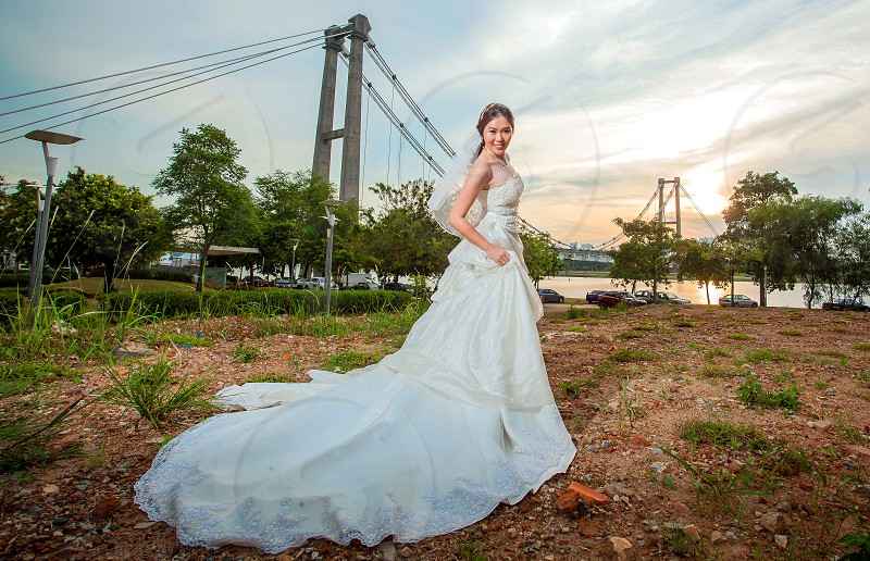 woman in white wedding dress standing on brown soil and green grass with beige concrete bridge background during golden hour photo
