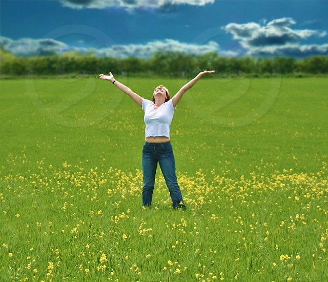 woman in white crew neck shirt and blue denim jeans standing on green field of grass and yellow flowers photo