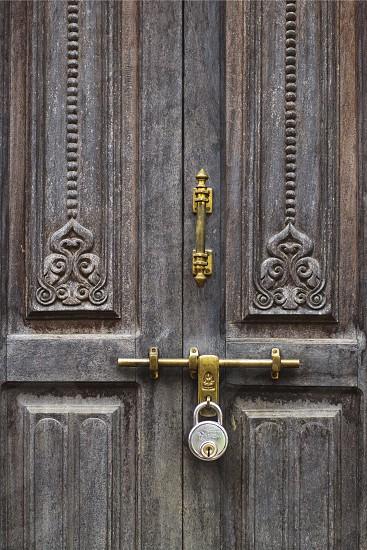 old dark wooden door with a metal lock photo