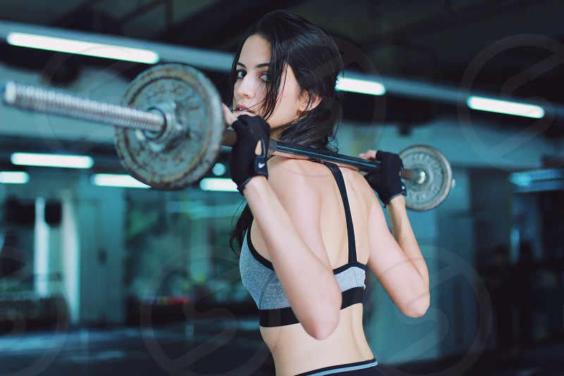 woman in grey sports bra carrying grey barbell photo