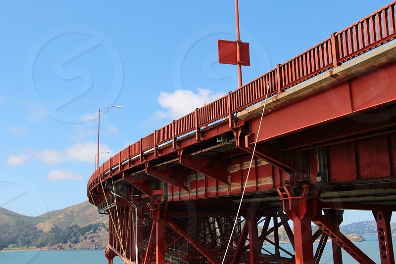 red metal curving trestle bridge over blue water with brown and green hills in distance under blue and white cloudy sky photo