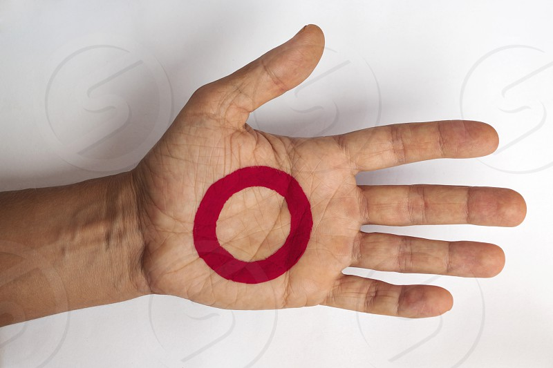 Man`s hand with painted red ring on it photo