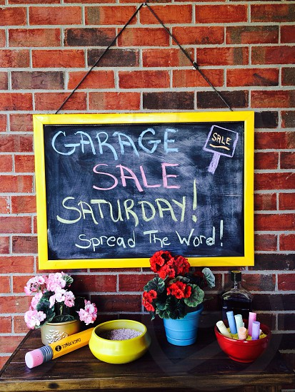 Chalkboard; brick wall; flowers; garage sale; chalk; yellow photo