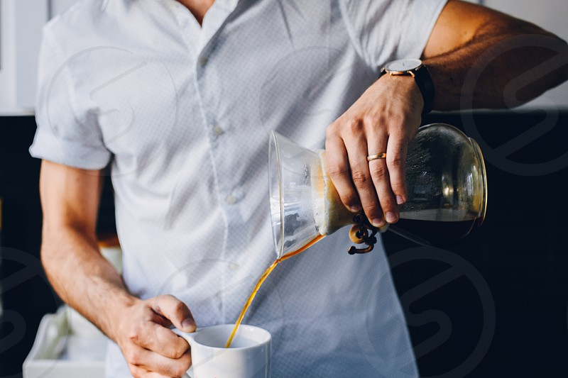 Young man pouring coffee in his home. photo