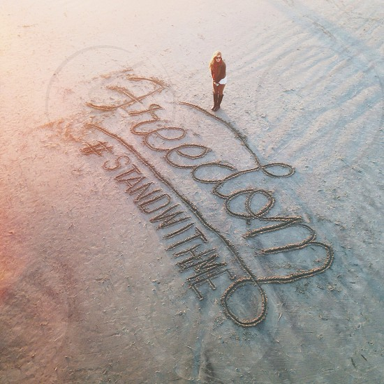 woman standing on a beach sand with a writing of freedom stand with me photo