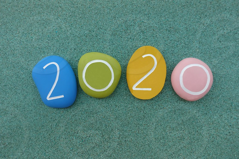 Year 2020 composed with colored stones over green sand                       photo