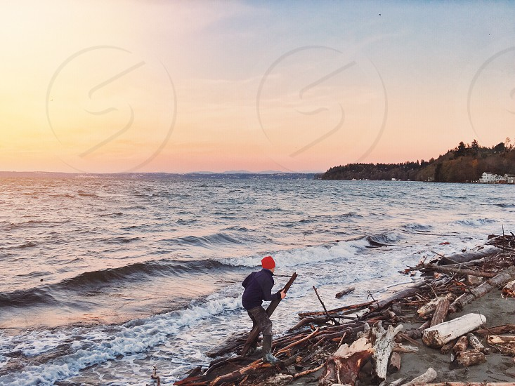 person in jacket and cap walking on drift wood covered beach with wood in their hand photo