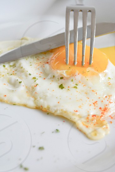 sunny side up egg with silver-colored fork on white plate photo