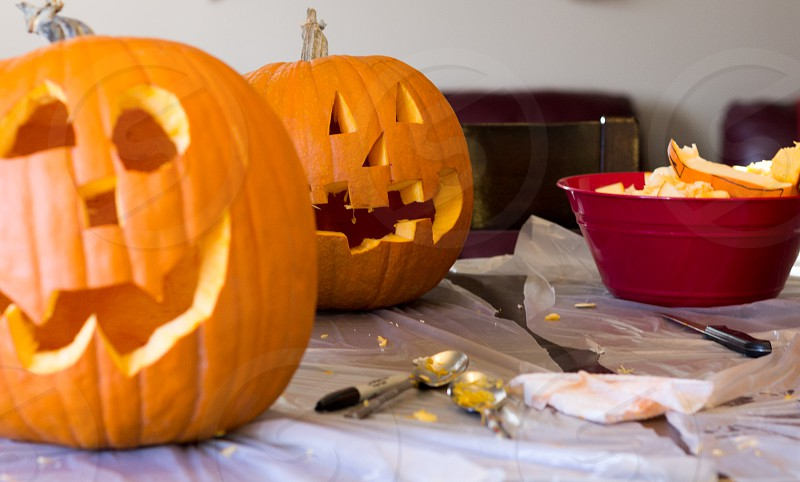 jack-o-lantern on table beside red plastic container photo