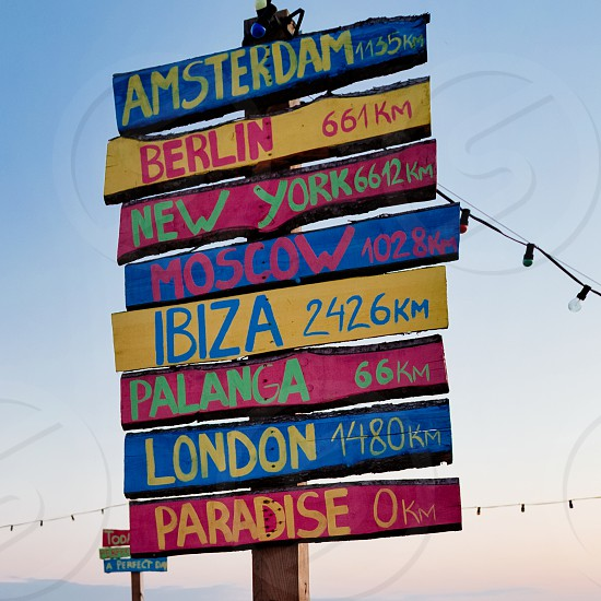 Colourful painted sign made of driftwood with city names and distance in kilometres on Liepaja beach Latvia photo