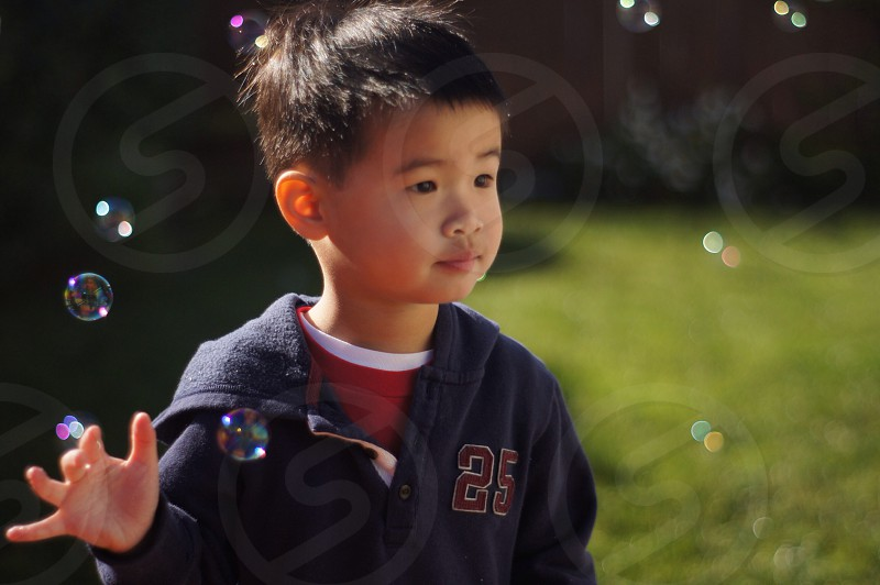 boy in blue zip up 25 hoodie on green grass playing with bubbles photo