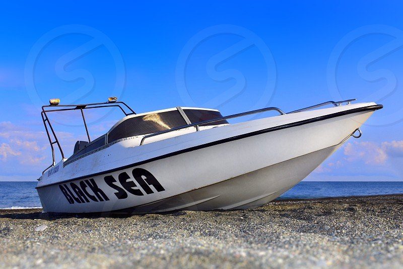 white black sea brand yacht on gray and black grained sand along body of water under clear blud photo