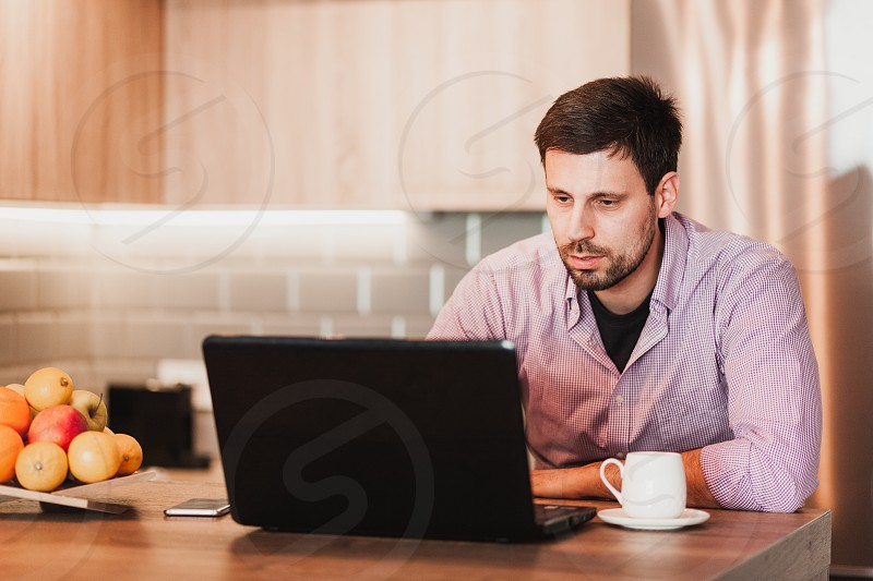 Young businessman working on a laptop at home photo