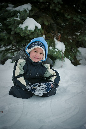 boy wearing black and grey snow suit sitting on snow covered ground with heart drawn on snow photo