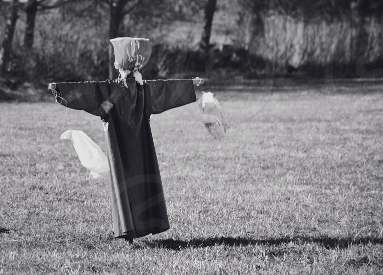Scarecrow scare crow scares off birds spooky spooks black and white object different photo