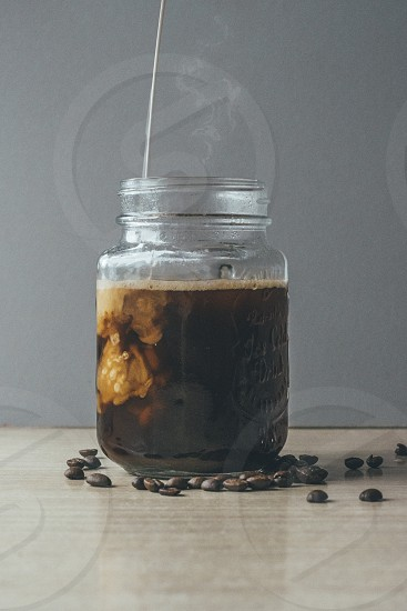 Glass jar of black coffee mixing with milk and roasted coffee beans on the table photo