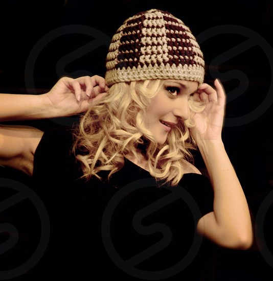 smiling blond woman with curly hair wearing brown and beige knit beanie and black short sleeve blouse with hands up touching hat against black background photo