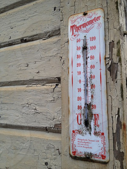 white and red thermometer on wooden panel reading 10 degrees celsius photo