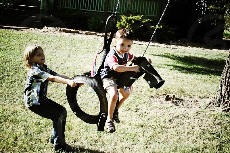 boy being pushed while on swing photo