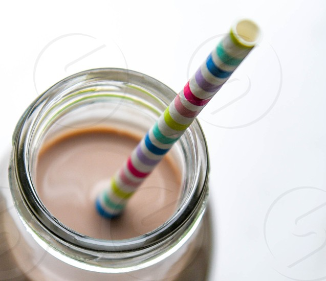 clear glass jar with brown liquid and multi colored stripe straw photo
