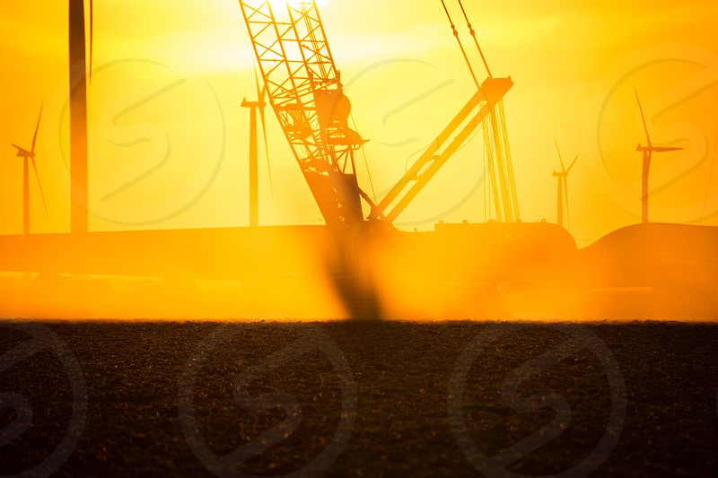 Crane heavy construction silhouette orange dust yellow brown field wind turbine windmill photo