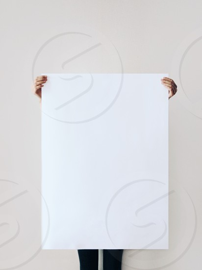person holding up white printer paper photo
