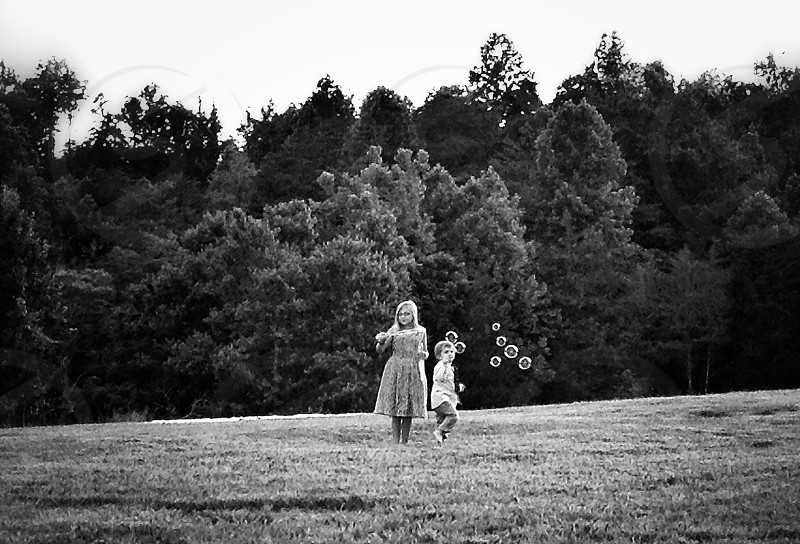 grayscale photo of girl and boy playing with bubbles on grass field photo
