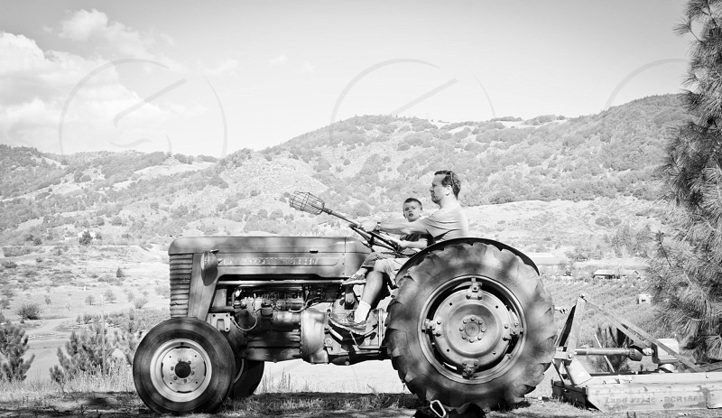 man and boy on tractor with view of hills behind during daytime photo