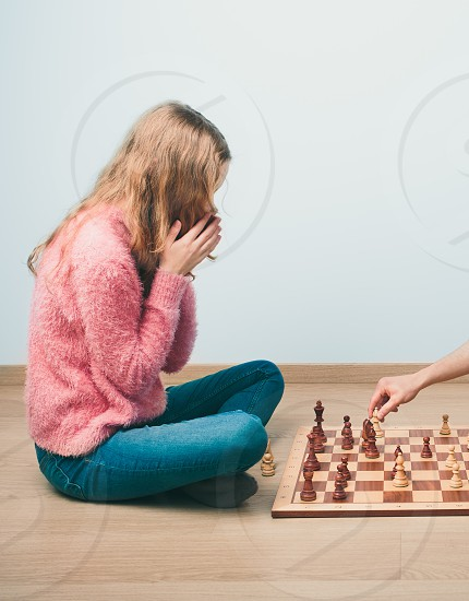 Checkmate. Girl is surprised by last move her opponent in chess game. Copy space for text at the top and bottom of image photo