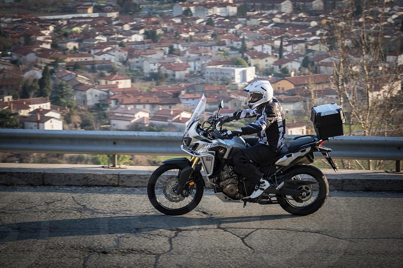 person in black and white suit wearing white full faced helmet riding white and black standard motorcycle with cargo box carrier on gray asphalt road with gray metal railings photo