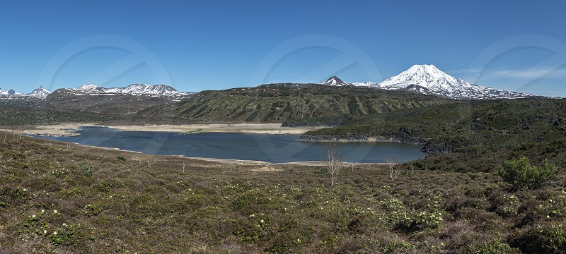 Panorama: beautiful mountain (volcanic) landscape of Kamchatka Peninsula: view of mountain lake and active Ichinsky Volcano on a sunny day. Far East Russian Federation. photo