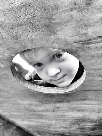 boy face on wood hole gray scale photography photo